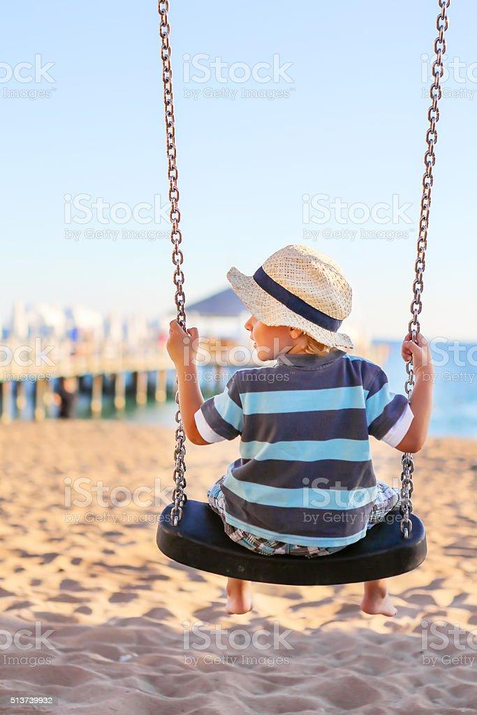 Funny toddler boy having fun on swing stock photo
