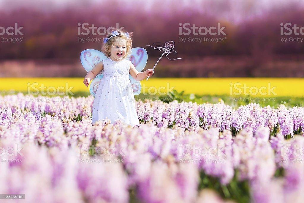 Funny toddler girl in fairy costume on flower field stock photo