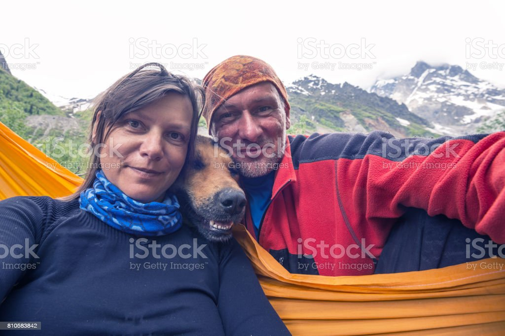 Funny travelers with big smiling dog, taking selfie on the background...