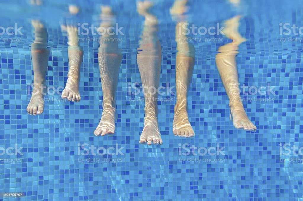 Funny underwater family legs in swimming pool stock photo