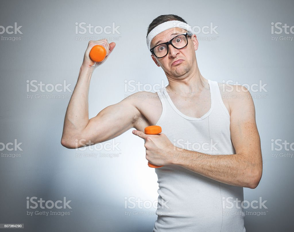 Funny weak man lifting biceps stock photo
