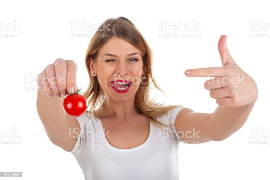 Funny woman holding cherry tomato stock photo