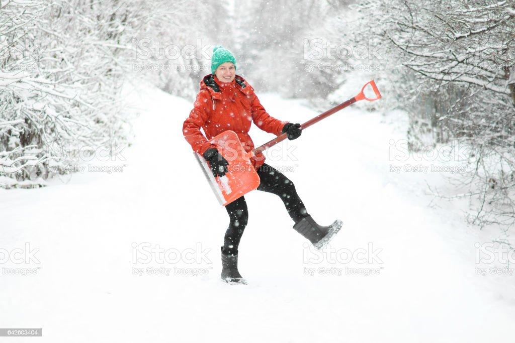Funny woman holding snow shovel like a guitar stock photo