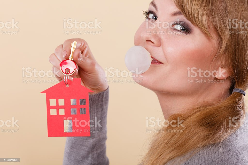 Funny woman holds house keys eat chewing gum stock photo