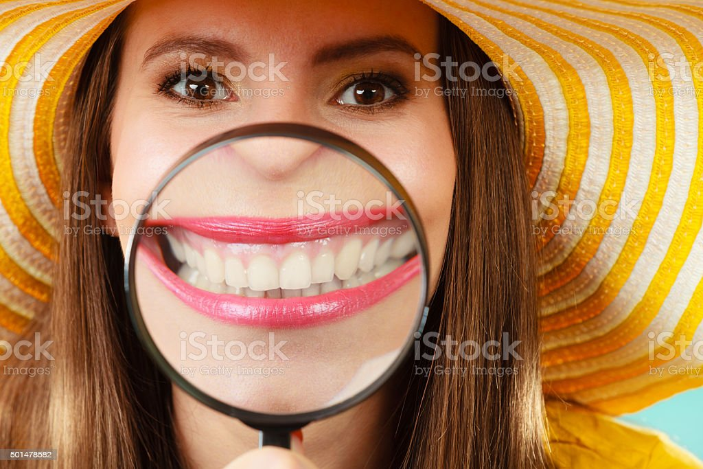 funny woman show teeth through magnifying glass stock photo