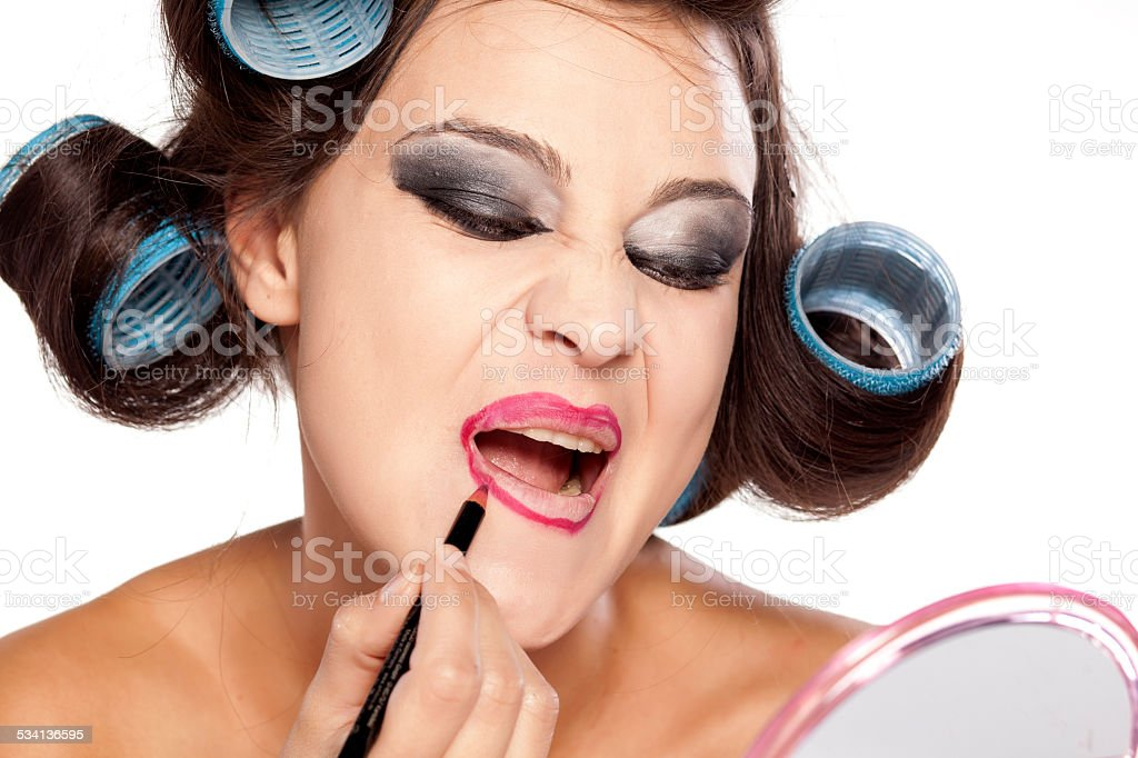 Funny woman with curlers and bad makeup applying lip pencil stock photo