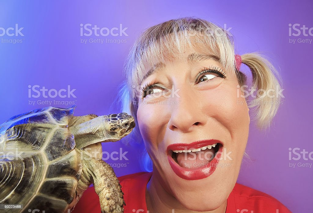 Funny woman with tortoise on vivid color background stock photo
