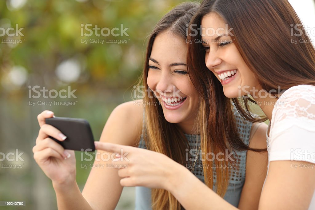 Funny women friends sharing media in a smart phone stock photo