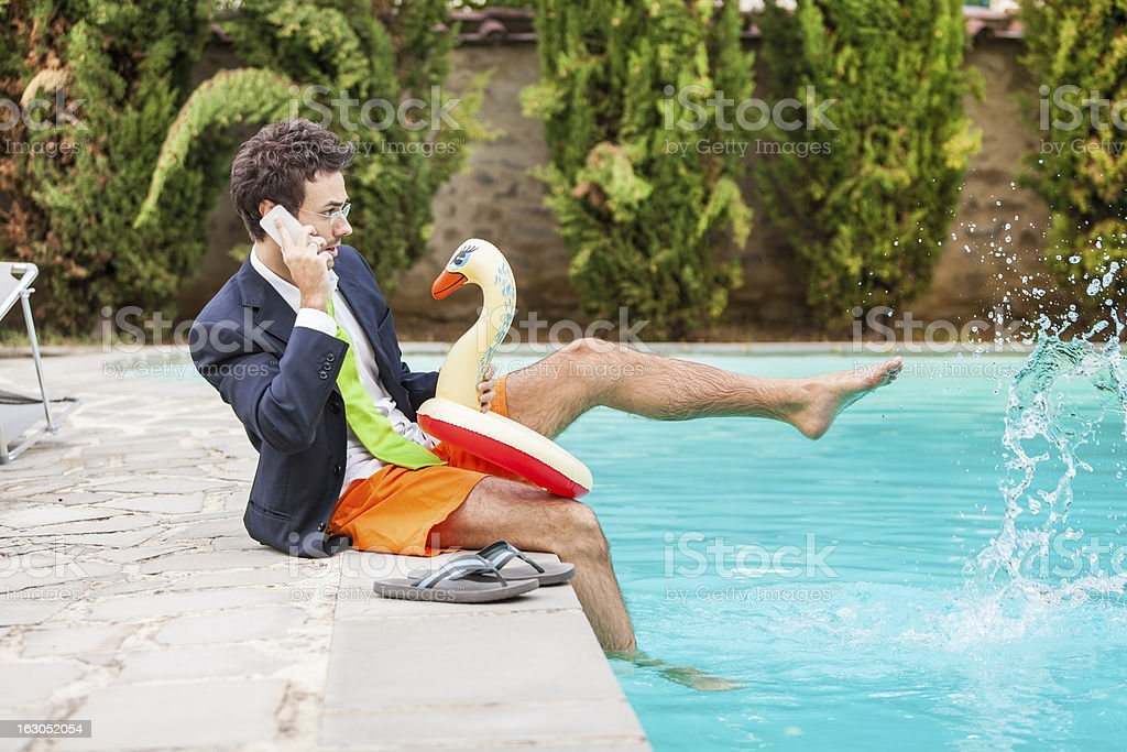 Funny Young Businessman with SwimmingTrunks next to the Pool royalty-free stock photo