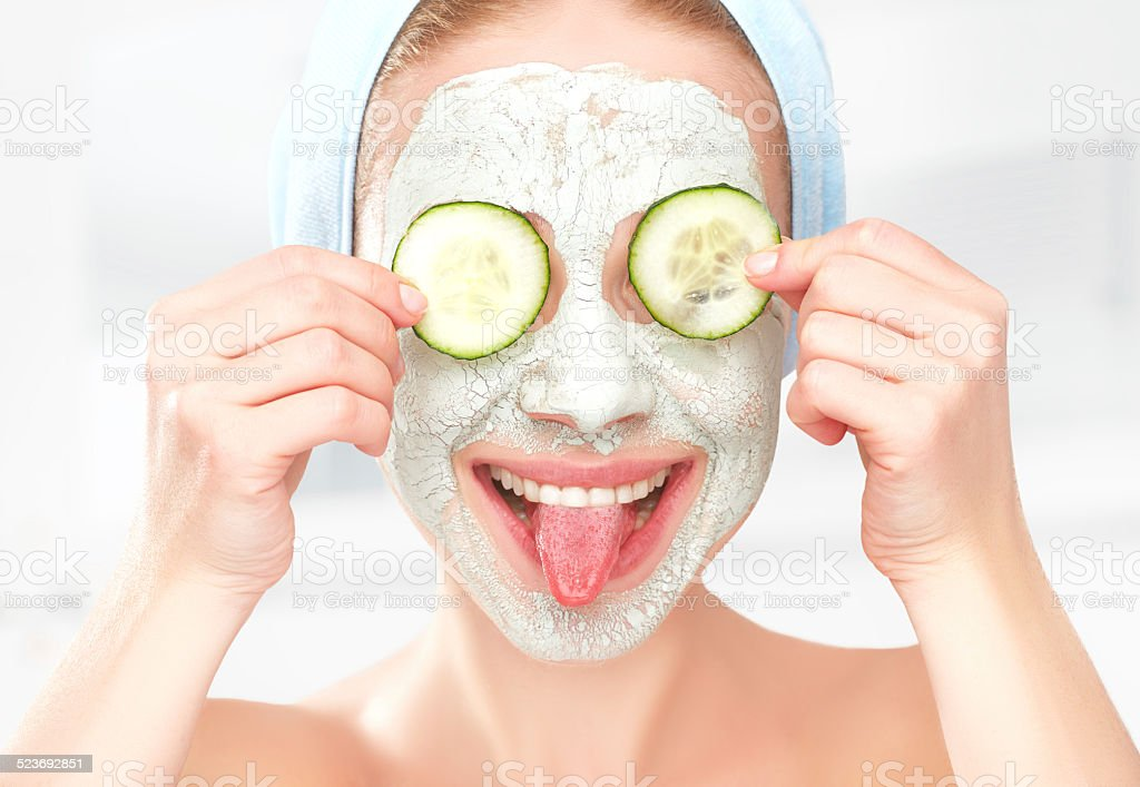 Funny young girl with a mask for skin face stock photo