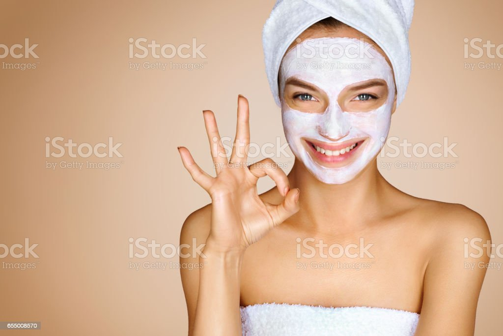 Funny young girl with moisturizer cream mask showing gesture okay. stock photo