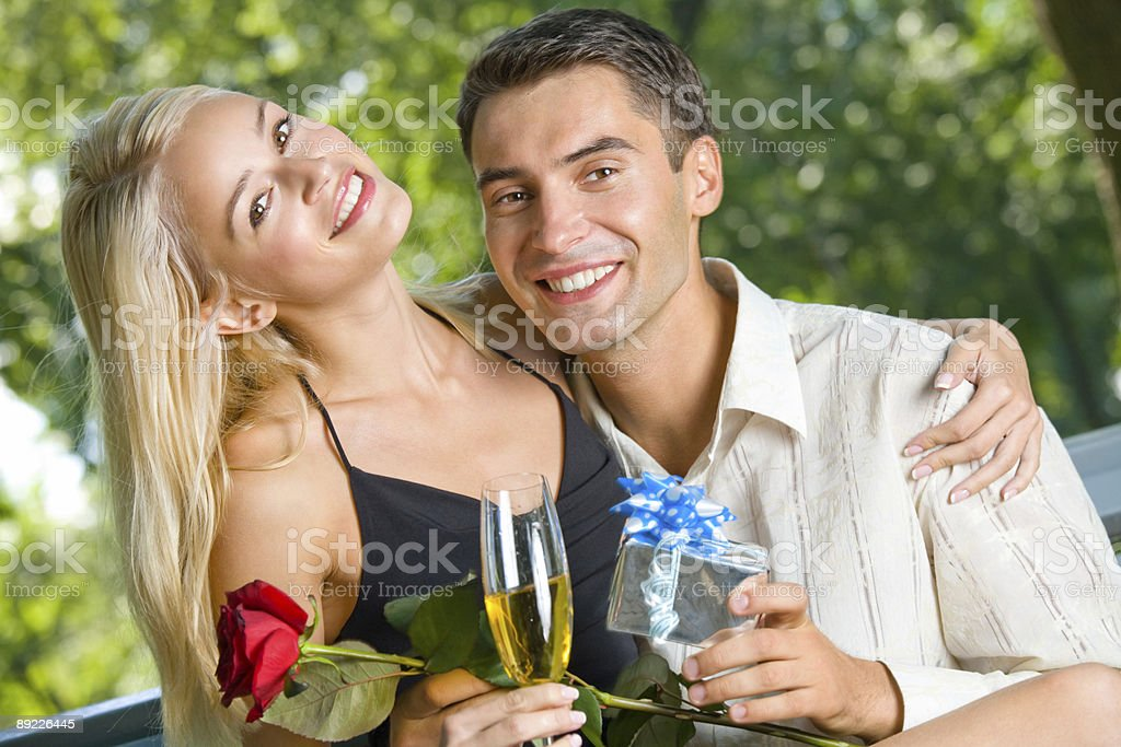 Funny young happy couple with gift and rosa, outdoors