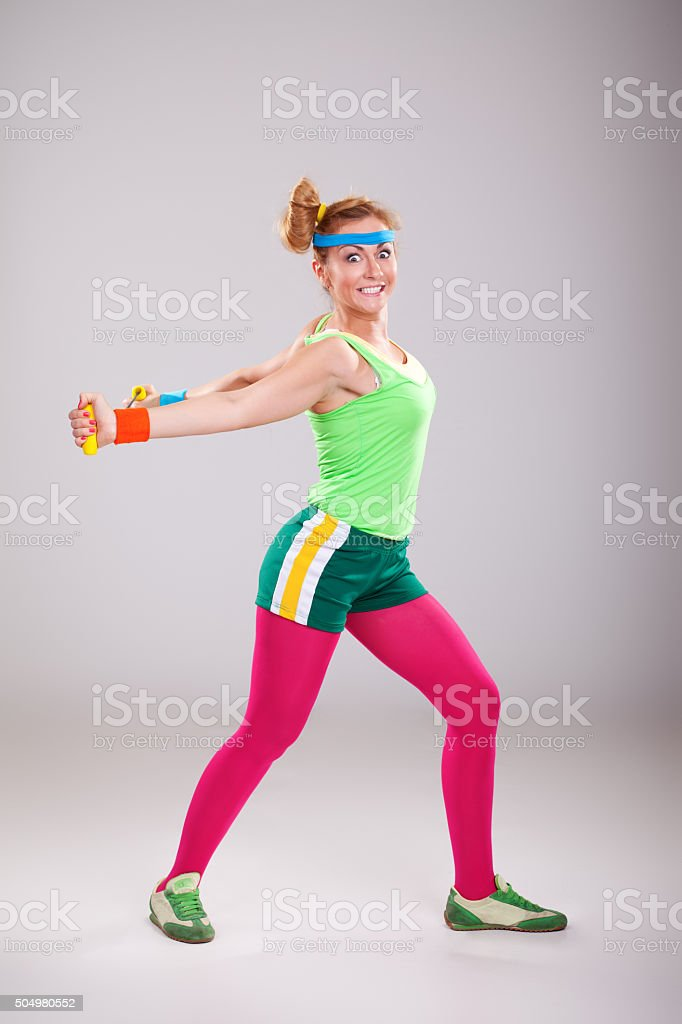 Funny young woman doing stretching exercises with resistance band stock photo