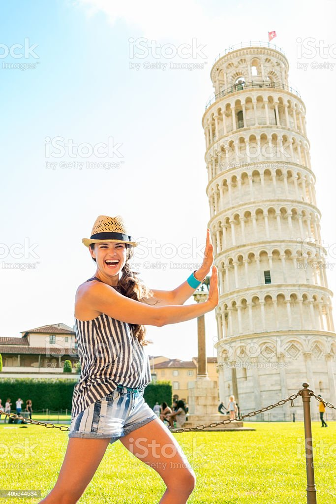 funny young woman supporting leaning tower of pisa, tuscany, italy stock photo