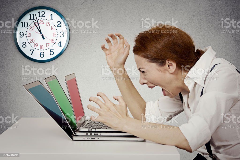 Furious, angry businesswoman screaming at computer, pissed off has nervous breakdown can't take it anymore stock photo