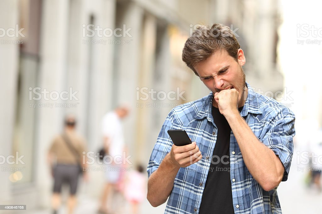 furious angry man watching mobile phone stock photo