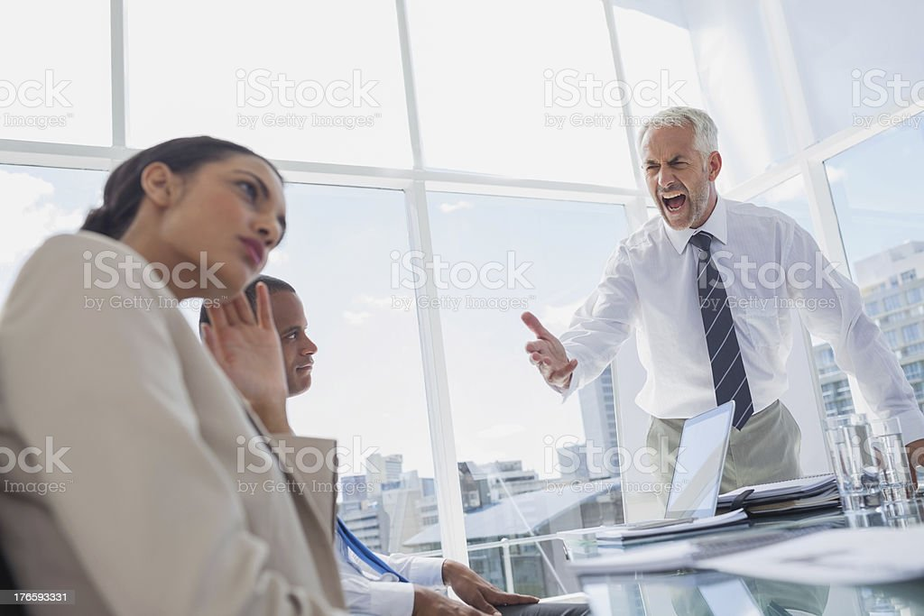 Furious boss yelling at colleagues stock photo