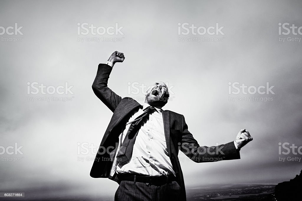 Furious, frustrated businessman shouting and gesturing defiantly against stormy sky stock photo