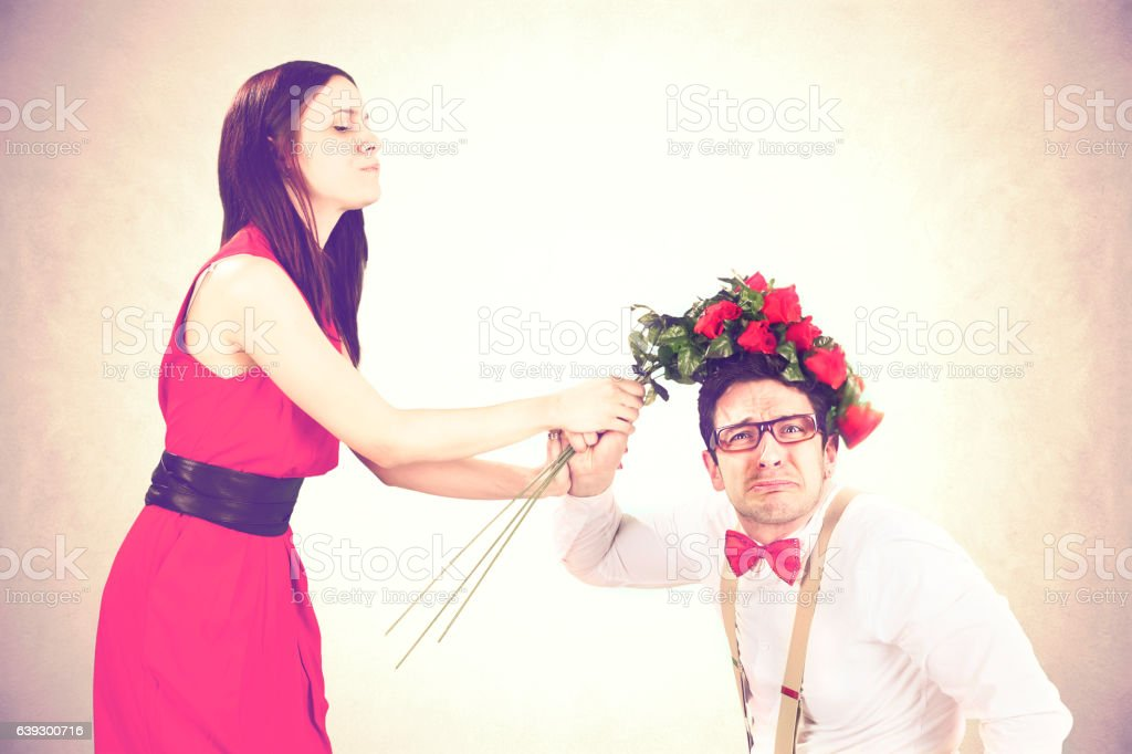 furious girl beating her boyfriend with roses stock photo