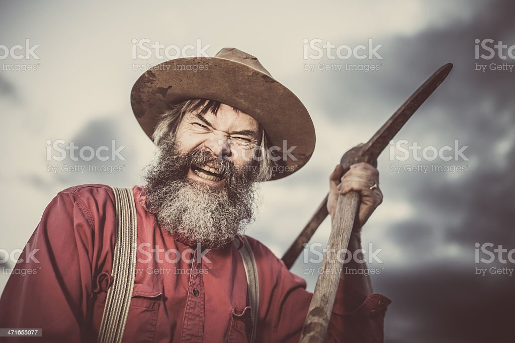 Furious Gold Miner with Pickaxe stock photo