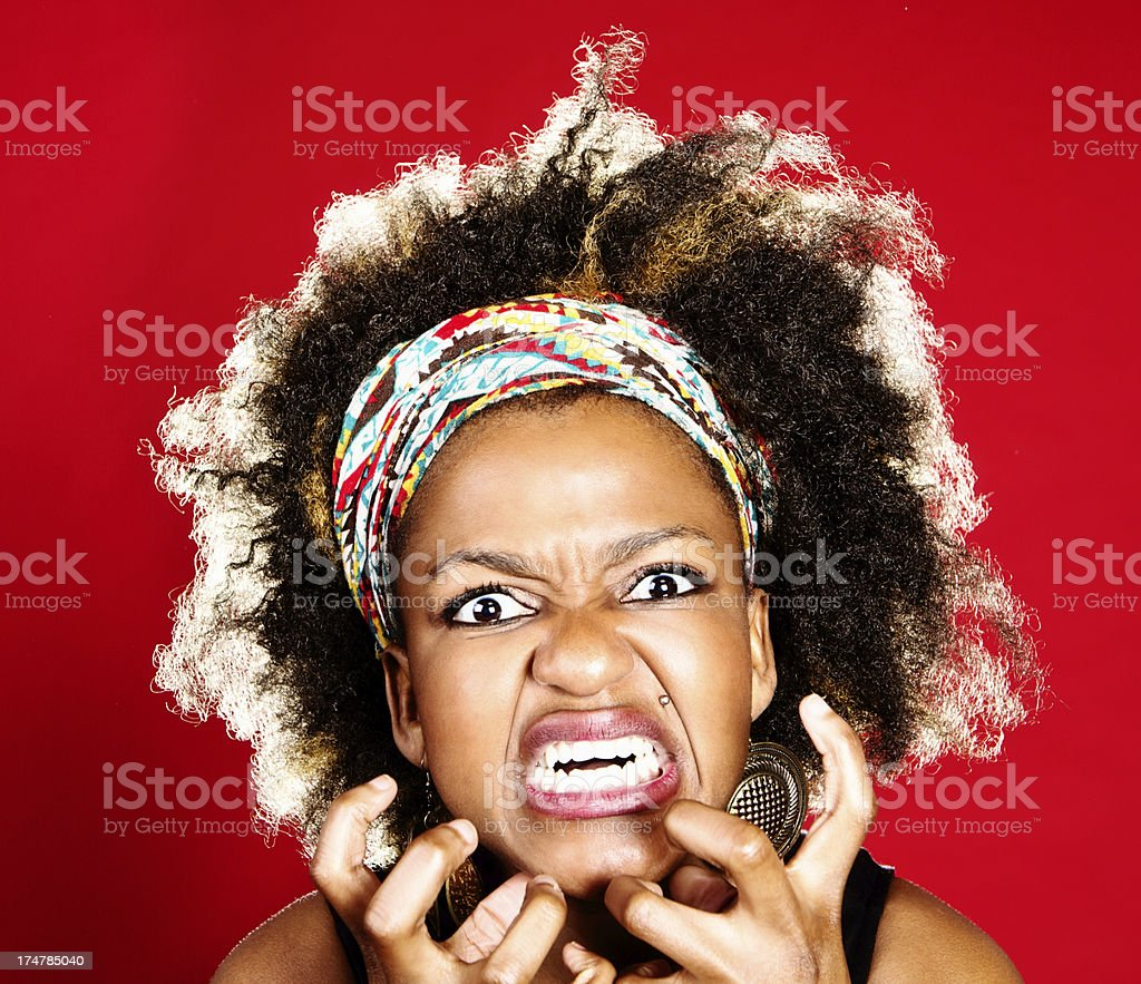Furious, grimacing young woman snarls and gesticulates in rage royalty-free stock photo