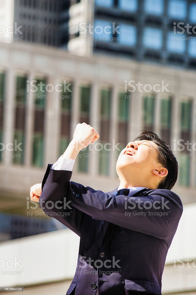 Furious Japanese man makes obscene gesture at sky stock photo