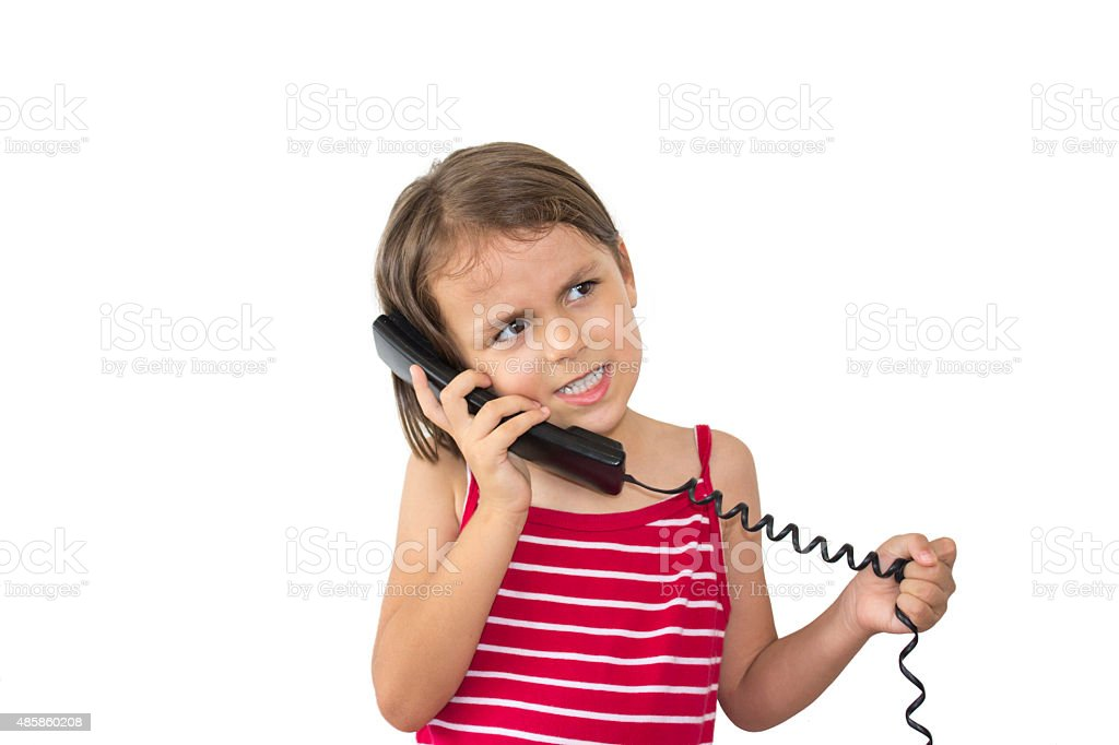 Furious little girl talking on phone with negative facial expres stock photo