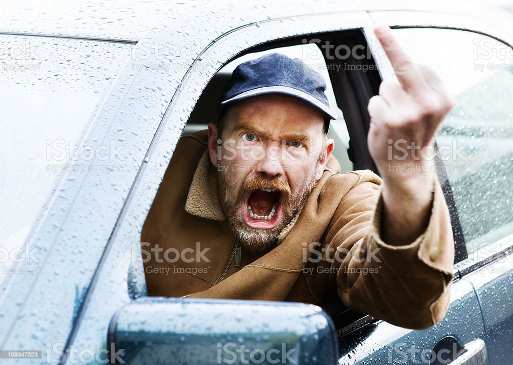 Furious male driver makes obscene gesture and shouts stock photo