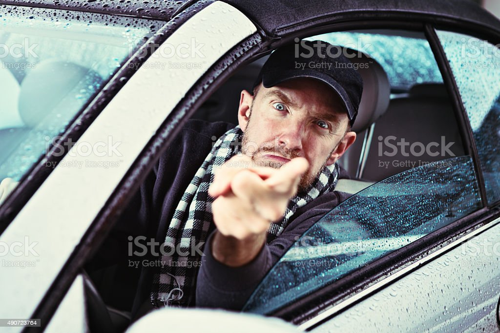 Furious man driving on rainy day points angrily through window stock photo