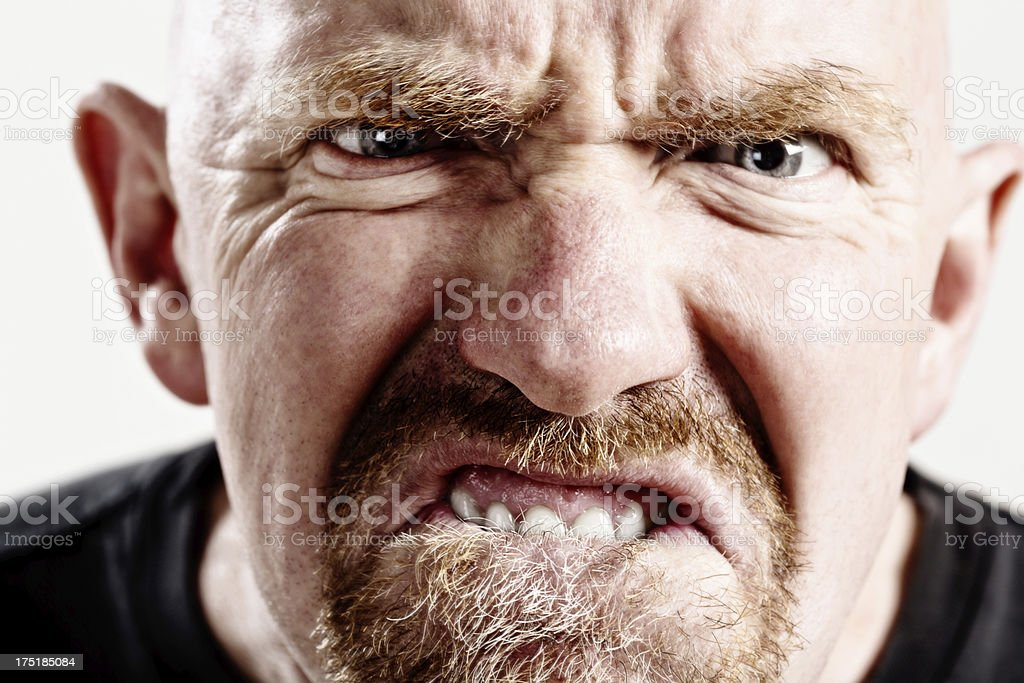 Furious mature man makes a hideously ugly and threatening face stock photo
