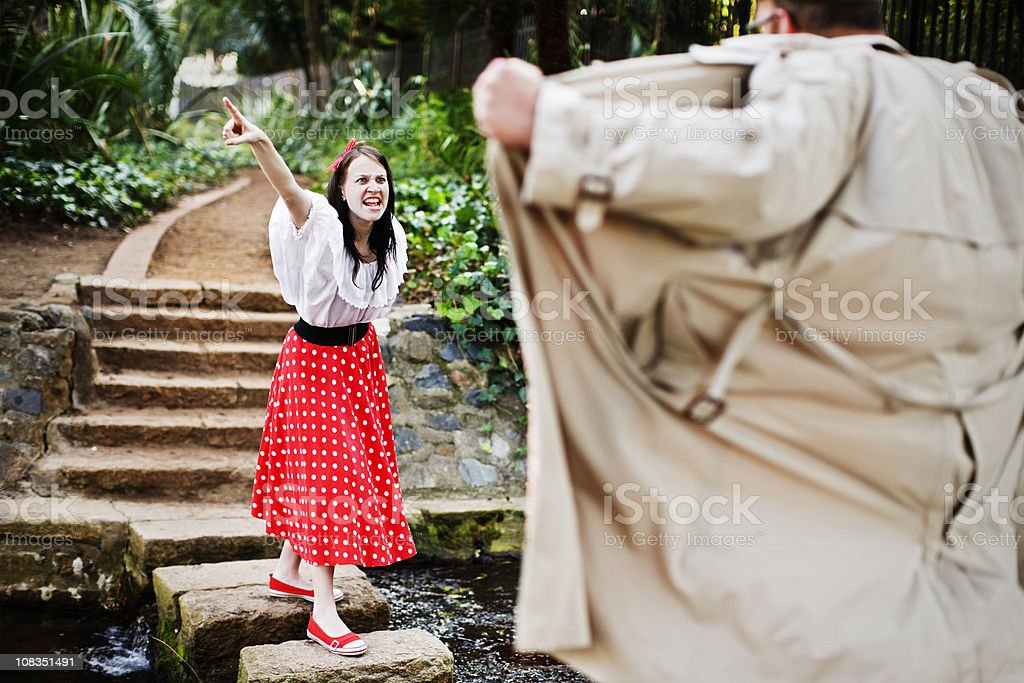 Furious young woman defies a flasher in the park royalty-free stock photo