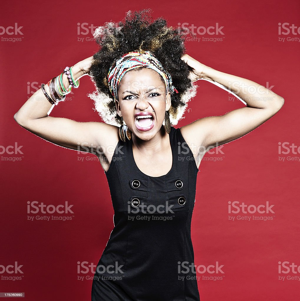 Furious young woman literally tearing her hair out royalty-free stock photo