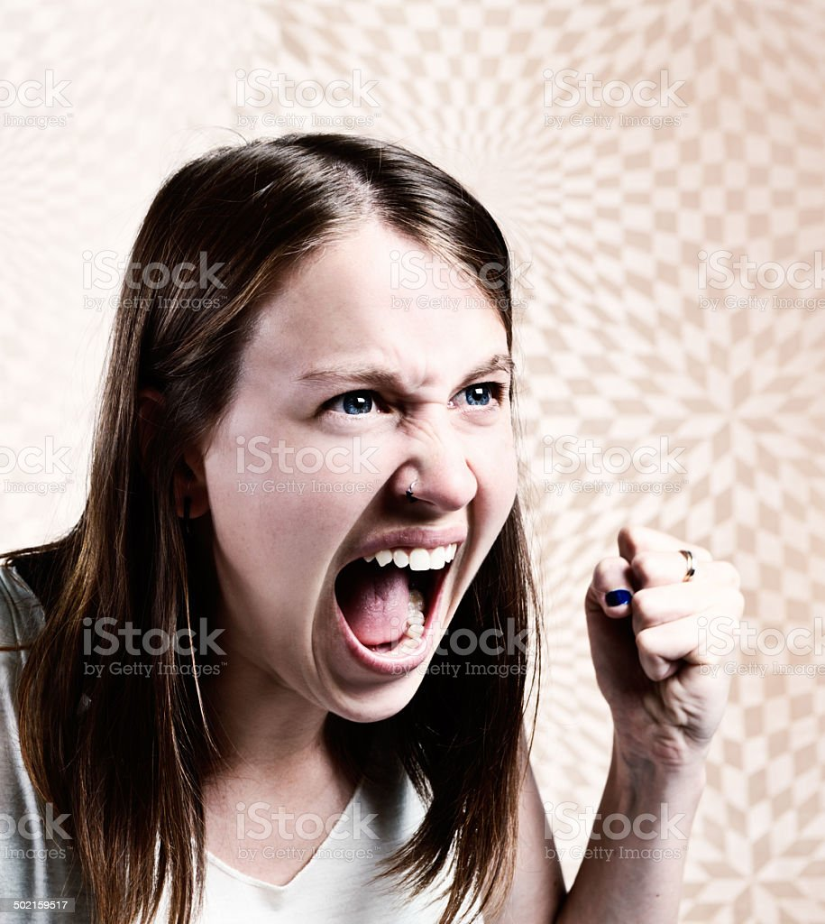 Furious young woman screams, shaking her first angrily stock photo