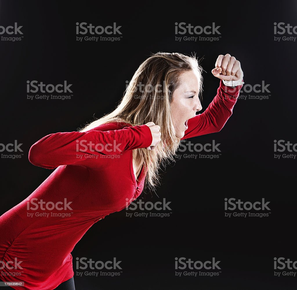 Furiously angry blonde in red leans forward, raging stock photo