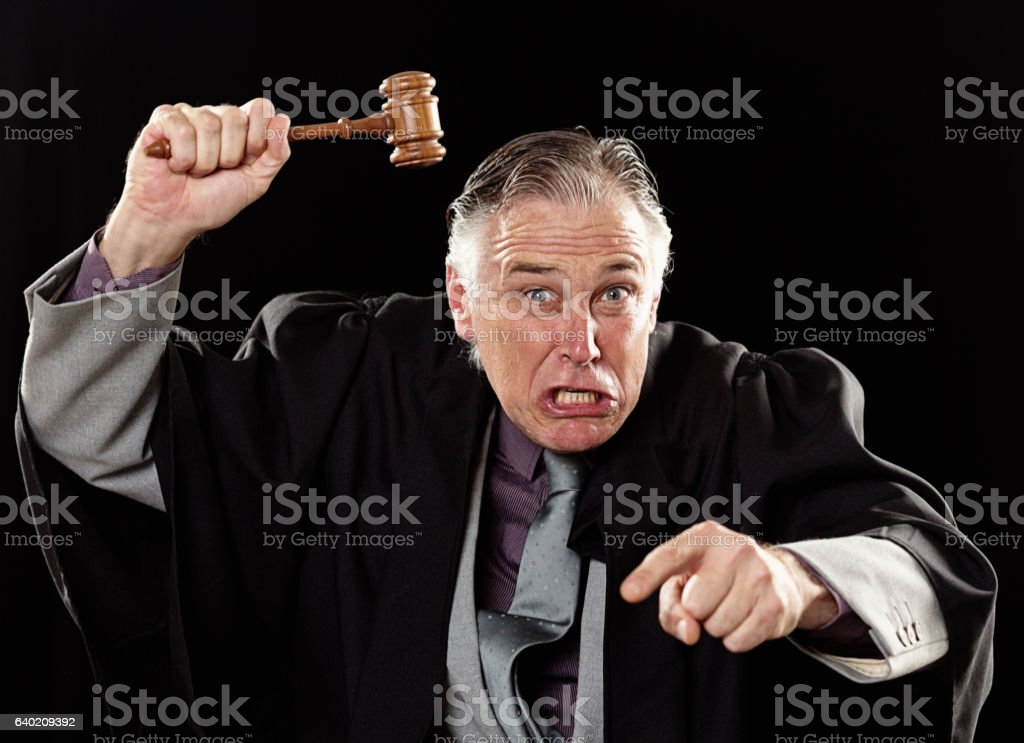 Furiously angry judge waves gavel, shouts and points threateningly stock photo