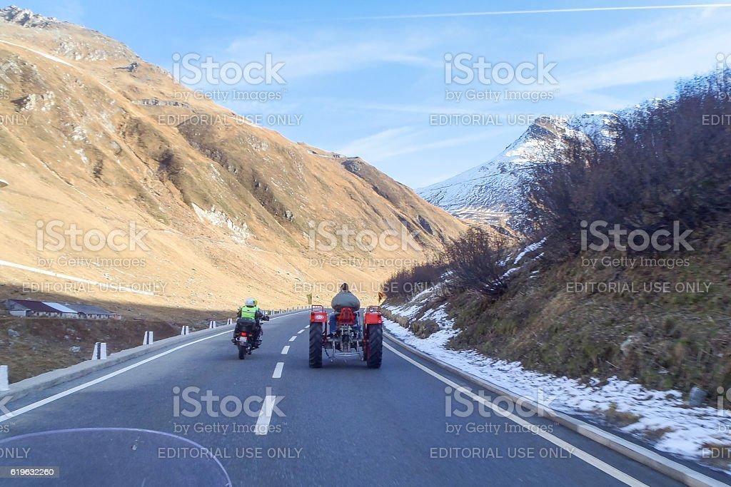 Furkapass. A motorcycle exceeds tractor stock photo
