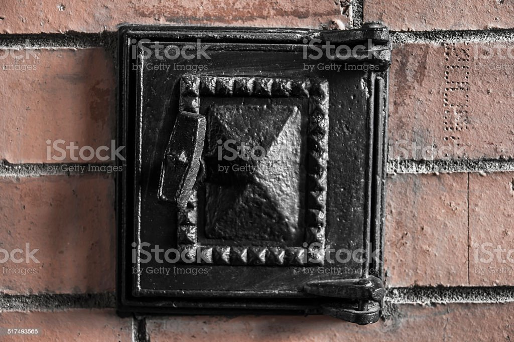 furnance iron black door on red brick oven wall stock photo