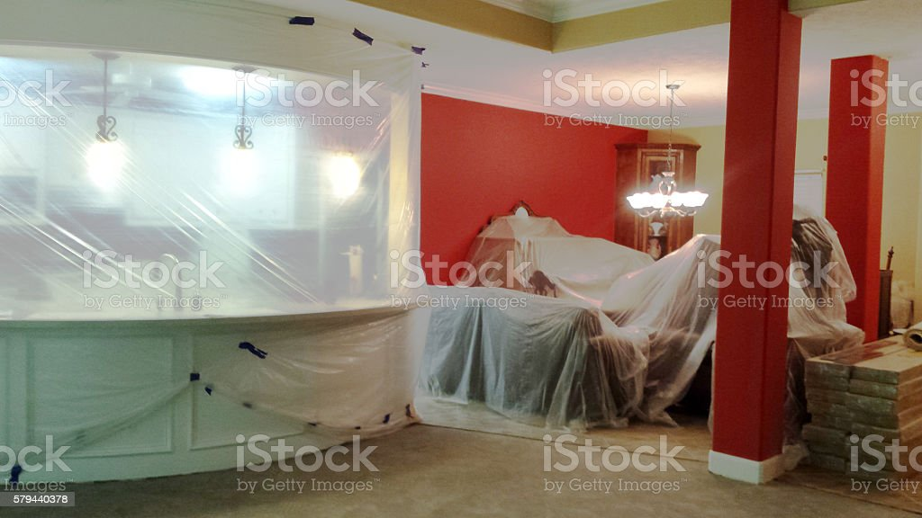 Furniture covered in plastic during home remodel project. stock photo