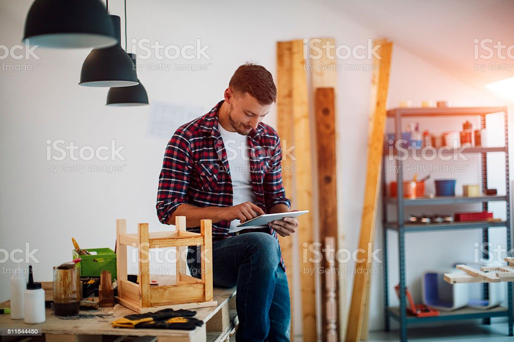 Furniture Designer Using Digital Tablet In His Furniture Workshop. stock photo