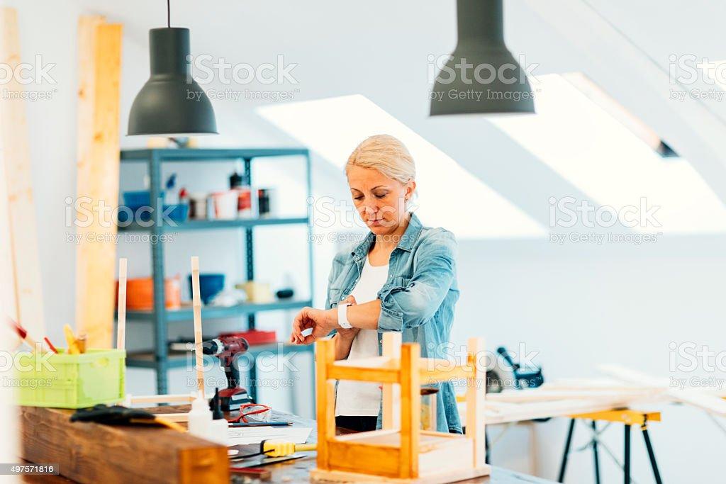 Furniture Designer Using Smart Watch In Her Workshop. stock photo