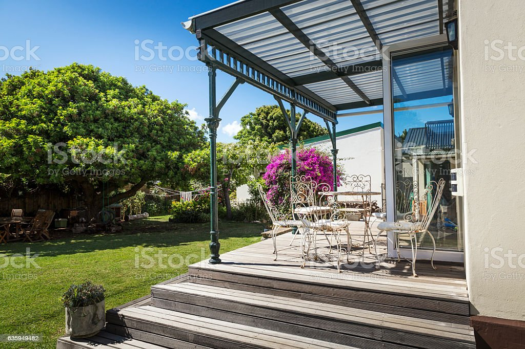 Furniture on porch by garden on sunny day stock photo