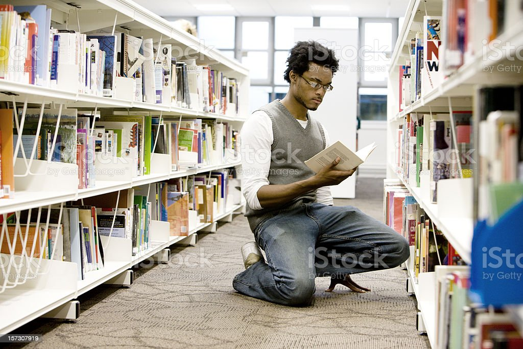 further education: a solitary student using his college library royalty-free stock photo