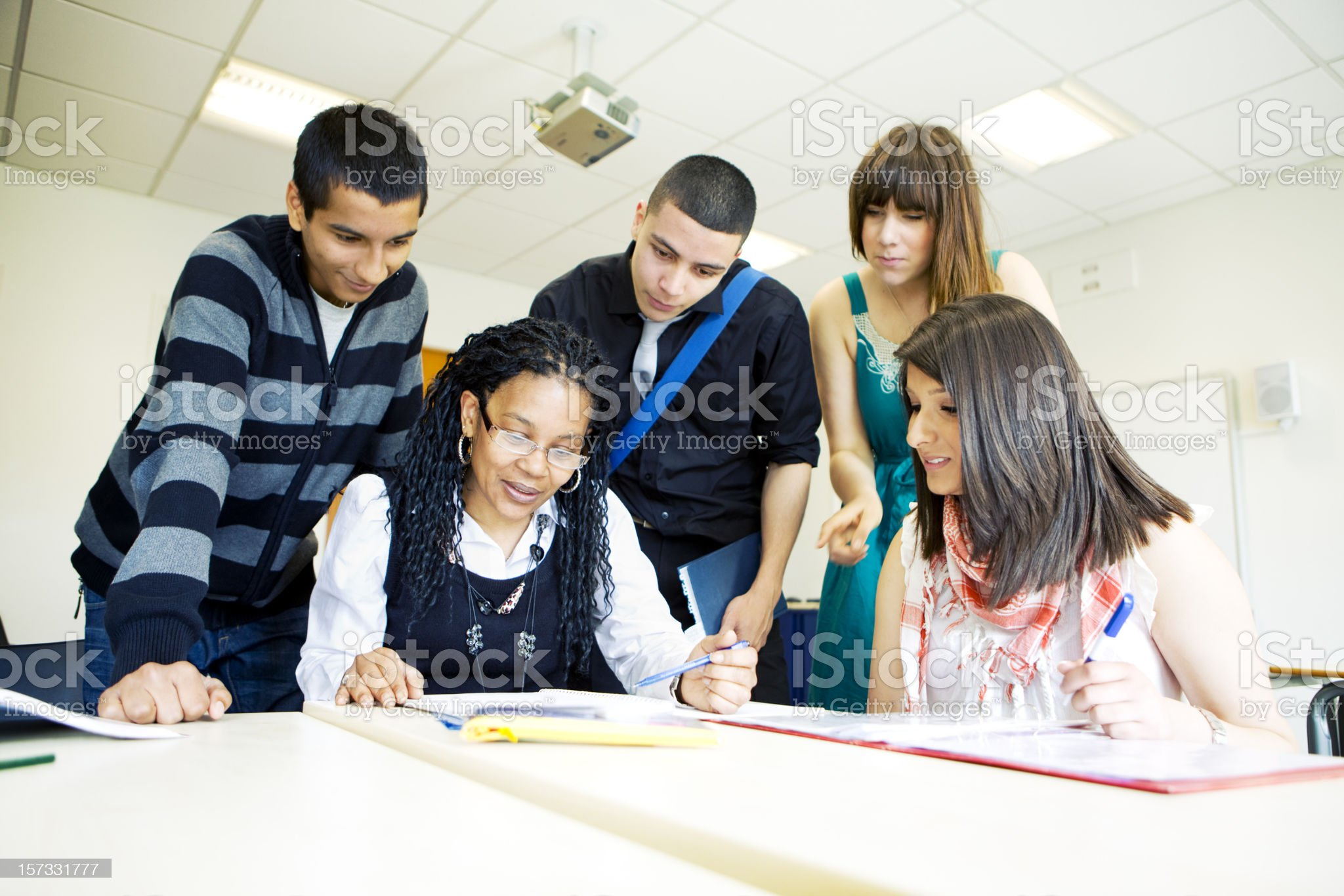 further education: diverse class tutorial with teacher helping her pupils royalty-free stock photo