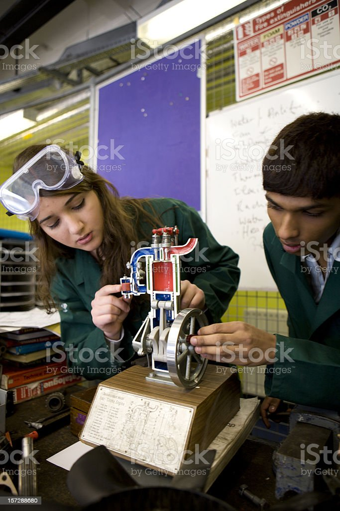further education: engineering classmates working together understanding combustion engines royalty-free stock photo