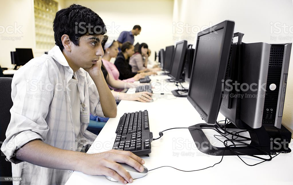 further education: Indian boy concentrating candidly on his computer studies royalty-free stock photo