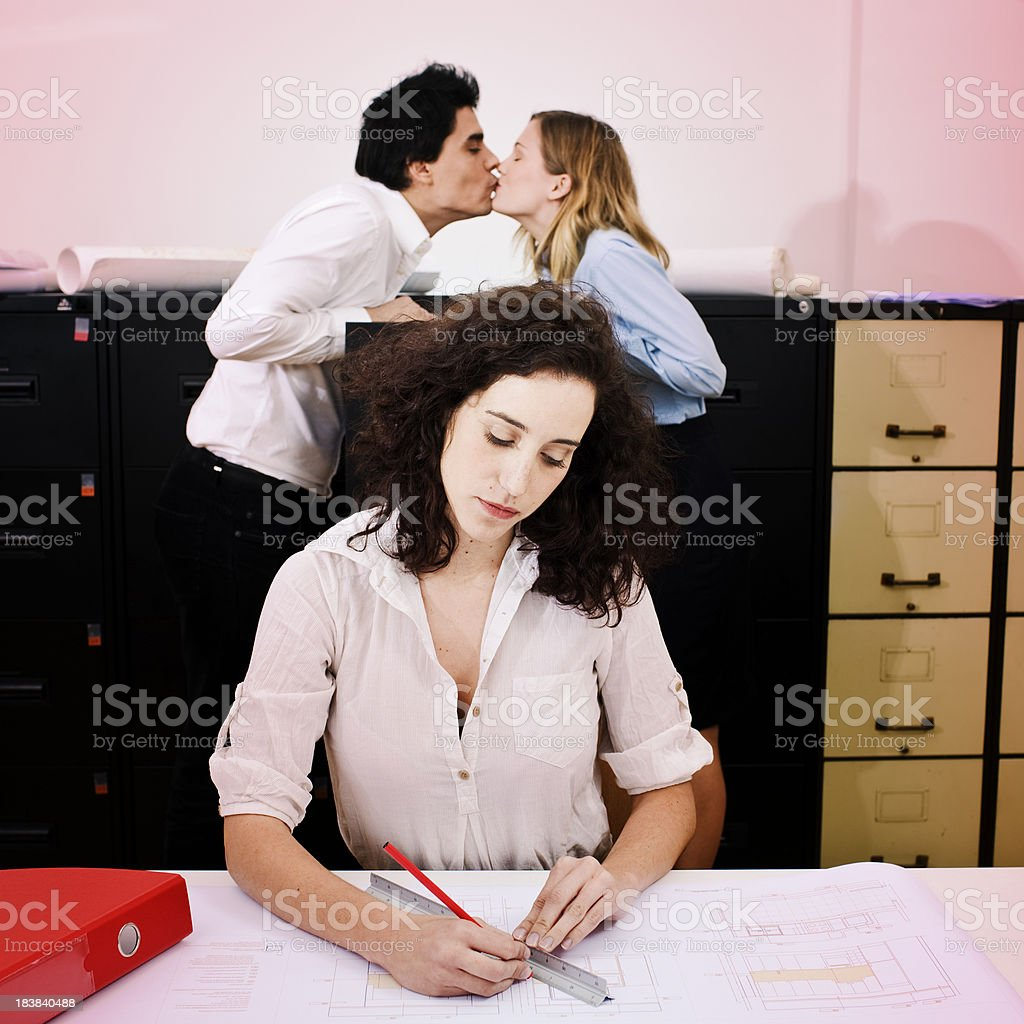 Furtive kiss in the ofice behind cooworker. royalty-free stock photo