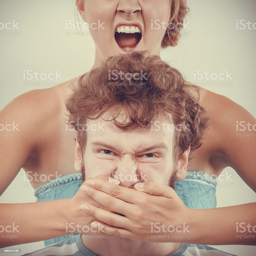 fury woman screaming while covering mouth her man stock photo