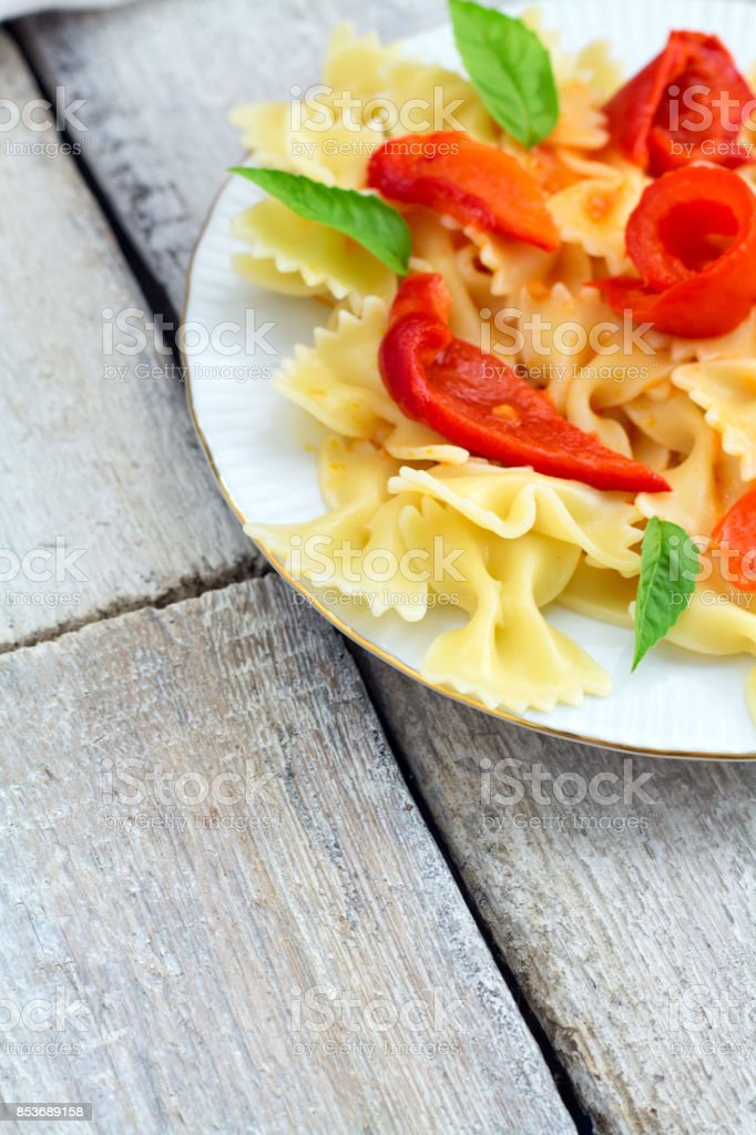 Fusilli pasta with pepper, tomatoes and herbs on old rustic background. Top view stock photo