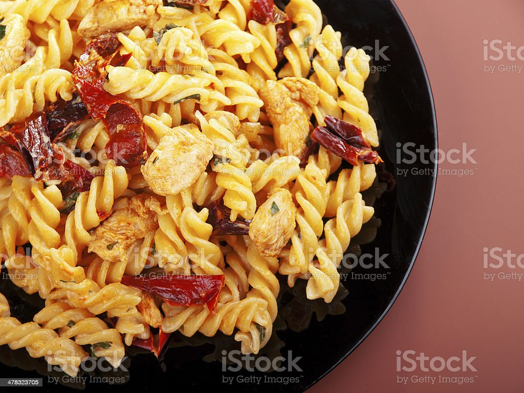 Fusilli with chicken and dried tomatoes royalty-free stock photo