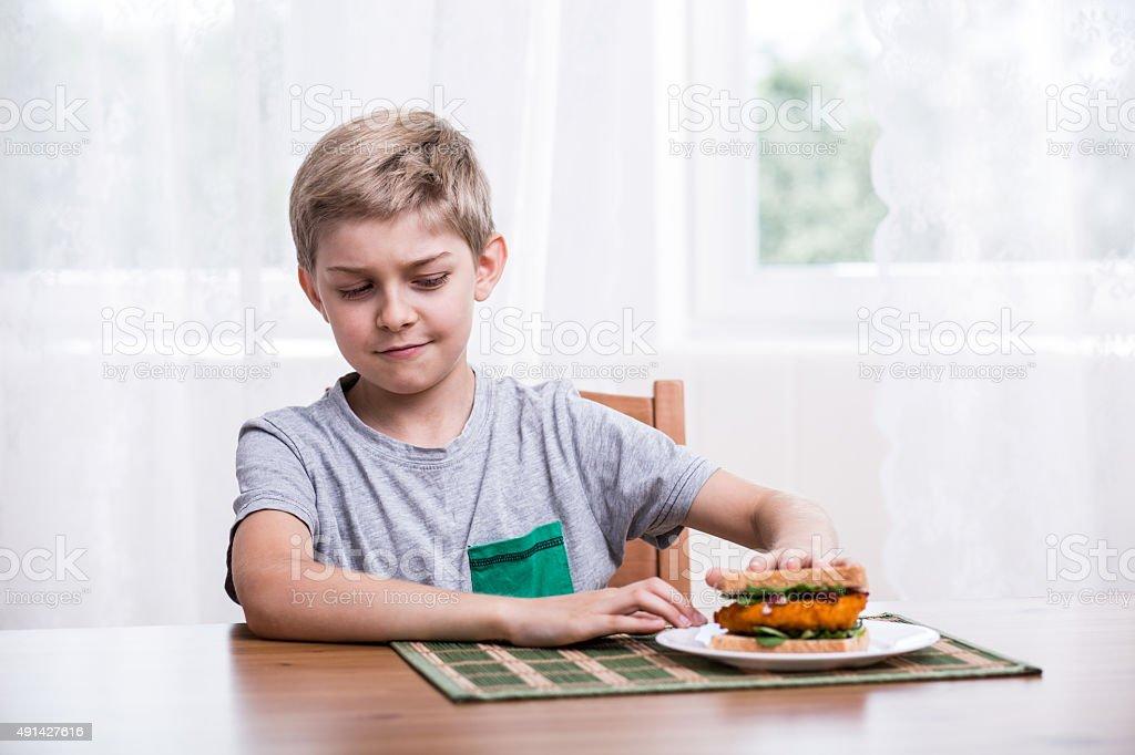Fussy kid with chicken sandwich stock photo